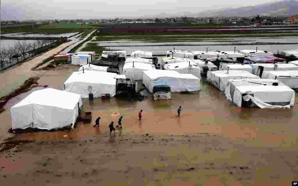 Syrian refugees make their way through a flooded temporary camp in Al-Faour, Lebanon, near the border with Syria.