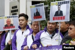 Members from Civic Party, holding portraits of (L-R) Wang Qingying, Yuan Chaoyang and Tang Jingling, protest outside China's Liaison Office in Hong Kong, China, Jan. 29, 2016.