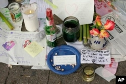 Candles burn and notes are left at a makeshift memorial near the site of a warehouse fire Wednesday.