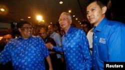 نجیب رزاق نخست وزیر مالزی(نفر وسط) پس از پایان رای گیری در آن کشور، ۶ مه ۲۰۱۳