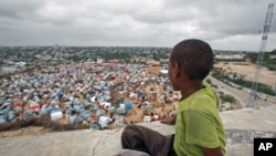 A boy sits looking over the Seyidka settlement for the famine stricken internally displaced people in Berkulan near Somalia's capital, Mogadishu, September 6, 2011.