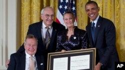 El ex presidente Bush y el presidente Obama entregan el premio 5.000 del programa de voluntarismo Daily Point of Light a Floyd Hammer y Kathy Hamilton.