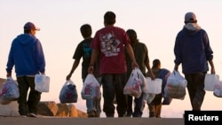 Un grupo de inmigrantes agrícolas regresan a su campamento en las afueras de San Diego, California.