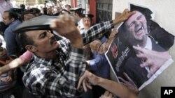 Un manifestant frappant un portrait du président syrien à l'aide sa chaussure devant l'ambassade de Syrie au Caire