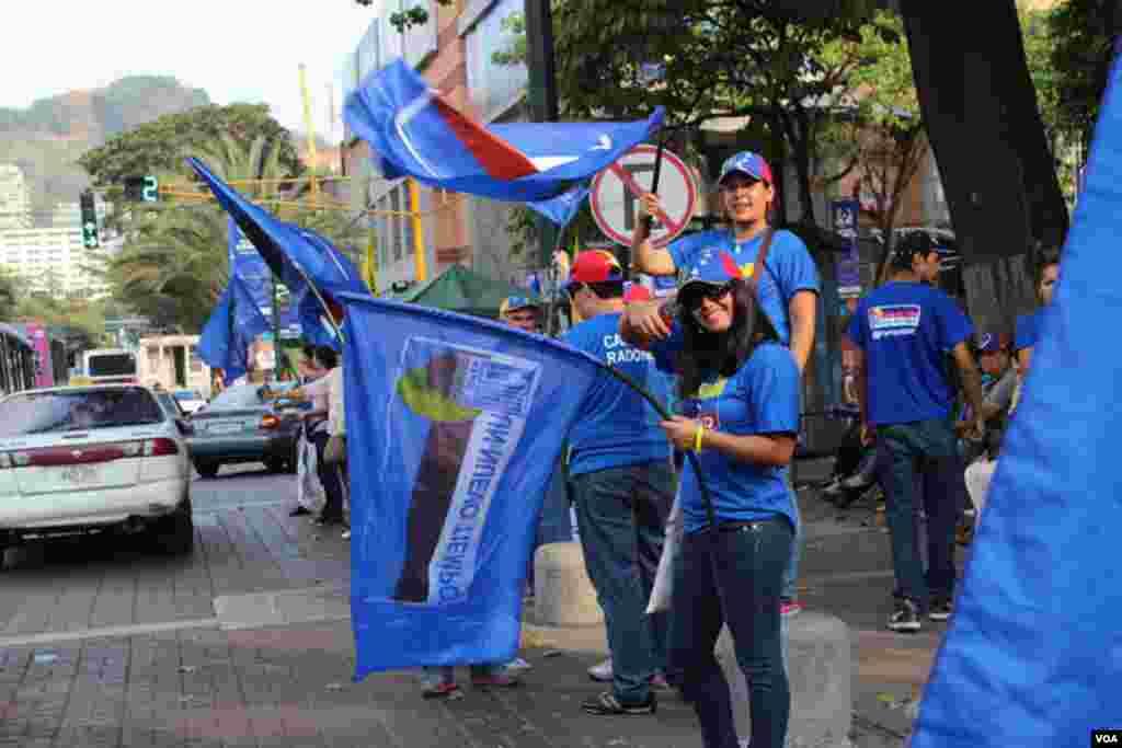"""Jóvenes que apoyan a Henrique Capriles, del llamado """"Un nuevo tiempo"""", saludan a los conductores en Caracas. [VOA]"""