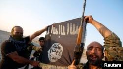 Militantes muestran la bandera del grupo extremista Estado Islámico.