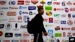FILE - a man walks by a billboard displaying a Chinese company developed packaging machinery for local and foreign food and beverage companies at the International soybean exhibition in Shanghai.