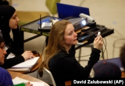 Gwyneth Glissmann of Boulder, Colorado, uses a special device to answer a question in the physics class of Professor Michael Dubson at the University of Colorado in Boulder, Colorado during his lecture.