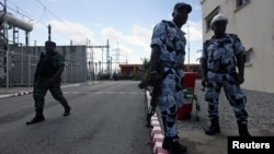 Ivorian soldiers stand guard at the Azito thermal power plant in the Yopougon district of western Abidjan, October 15, 2012.