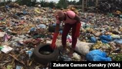 Aïcha Traoré, jeune créatrice, ramasse des pneus usés dans une décharge, à Conakry, Guinée, 13 septembre 2018. (VOA/ Zakaria Camara Conakry)
