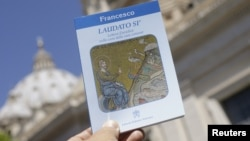 "Pope Francis' new encyclical titled ""Laudato Si (Be Praised), On the Care of Our Common Home"", is displayed during the presentation news conference at the Vatican, June 18, 2015."
