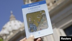 """Pope Francis' new encyclical titled """"Laudato Si (Be Praised), On the Care of Our Common Home"""", is displayed during the presentation news conference at the Vatican, June 18, 2015."""