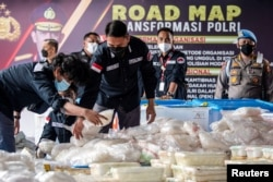 Indonesian police officers arrange drug evidence during a media conference, at the national police headquarters after officers managed to secure 2.5 tonnes of crystal methamphetamine from a network of the Middle East, Malaysia, and Indonesia, in Jakarta,