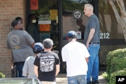 People wait outside a WIN job center in Pearl, Mississippi, April 21, 2020. WIN lobbies are closed statewide during the COVID-19 pandemic, but some staff continue to work with clients by providing unemployment benefits applications.
