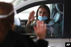 In this June 26, 2020 photo, U.S. District Judge Laurie Michelson, left, administers the Oath of Citizenship to Hala Baqtar during a drive-thru naturalization service in Detroit.