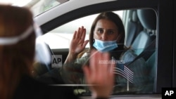 FILE - U.S. District Judge Laurie Michelson, left, administers the Oath of Citizenship to Hala Baqtar during a drive-thru naturalization service in Detroit.
