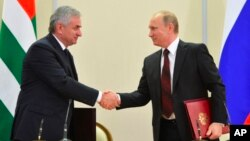 Russian President Vladimir Putin (r) and leader of Georgia's breakaway province of Abkhazia Raul Khadzhimba shake hands at a signing ceremony in the Bocharov Ruchei residence in Sochi, Russia, Nov. 24, 2014.