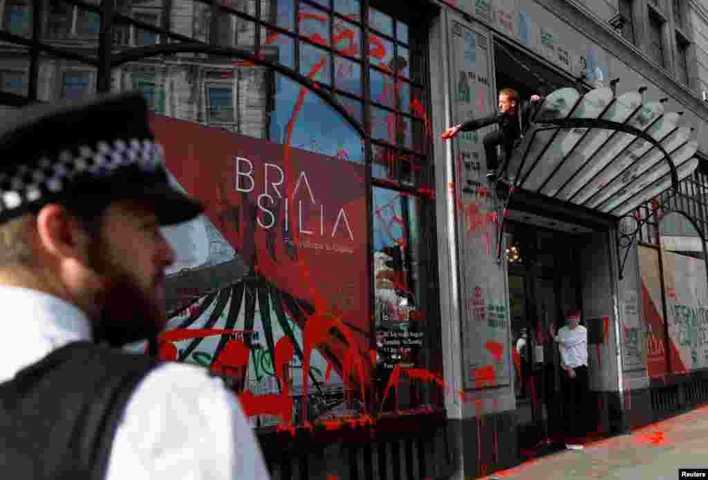 Um ativista joga uma pintura vermelha na fachada da embaixada brasileira em Londres durante um protesto contra a mudança climática.