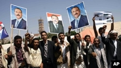 Yemeni men hold up portraits of President Ali Abdullah Saleh as they celebrate his return to Sana'a after more than three months of medical treatment in Saudi Arabia, even as his forces were battling dissident troops in the capital, September 23, 2011.