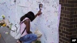 ایک خاتون آتشزدگی سے ہلاک ہونے والوں کی یاد میں افسردہ بیٹھی ہے