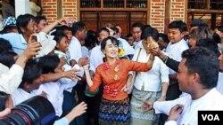 Aung San Suu Kyi menyalami pendukungnya di desa Kyit Tee, kota Myaing, Burma Tengah (31/1). Suu Kyi batal mengadakan kampanye di stadion sepakbola setempat.