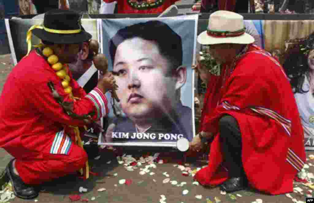 Shamans perform a ritual for good luck in 2012 as they hold up a poster of North Korea's next leader Kim Jong Un in Lima, Peru, Thursday Dec. 29, 2011. (AP Photo/Karel Navarro)