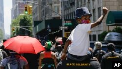 A man carries a child as they march near Central Park, during a Juneteenth celebration, June 19, 2020, in New York. Juneteenth commemorates when the last enslaved African Americans learned they were free 155 years ago.