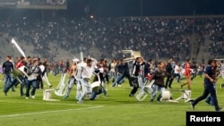 Besiktas fans throw plastic chairs onto the pitch during the Turkish Super League derby soccer match between Besiktas and Galatasaray at Ataturk Olympic Stadium in Istanbul September 22, 2013.