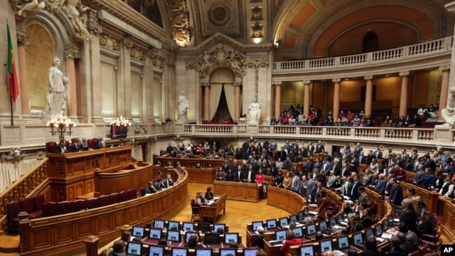 Members of parliament stand up, background right, to vote in favor of a bill that grants adoption rights to same-sex couples at the parliament in Lisbon, Feb. 10, 2016.