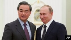 Russian President Vladimir Putin, right, shakes hands with Chinese Foreign Minister Wang Yi during their meeting in Moscow, Russia, March 11, 2016.
