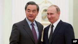 Presiden Rusia Vladimir Putin (kanan) berjabat tangan dengan Menlu China Wang Yi di Moskow, Rusia (11/3).
