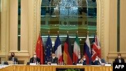 ພາບໃບນີ້ ໄດ້ຖືກເປີດເຜີຍໃນວັນທີ 1 ພຶດສະພາ 2021 ໂດຍຄະນະຜູ້ແທນຂອງສະຫະພາບຢູໂຣບ ຫຼື EU ໃນນະຄອນ ວຽນນາ ສະແດງໃຫ້ເຫັນບັນດາສະມາຊິກຂອງຄະນະຜູ້ແທນຈາກທັງສອງຝ່າຍ ໃນການເຂົ້າຮ່ວມກອງປະຊຸມ ກ່ຽວກັບຂໍ້ຕົກລົງ ດ້ານນິວເຄລຍຂອງອີຣ່ານ ຢູ່ໂຮງແຮມ Grand Hotel ໃນນະຄອນວຽນນາ.
