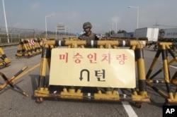 Binh sĩ Hàn Quốc đứng canh phía sau chướng ngại vật trên chiếc cầu dẫn đến vùng phi quân sự, gần làng biên giới Bản Môn Điếm.