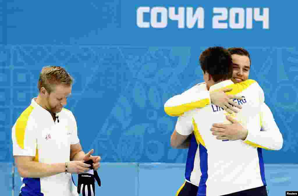 Sweden's second Fredrik Lindberg is congratulated as skip Niklas Edin stands after winning their men's bronze medal curling game against China at the Ice Cube Curling Center, Feb. 21, 2014.
