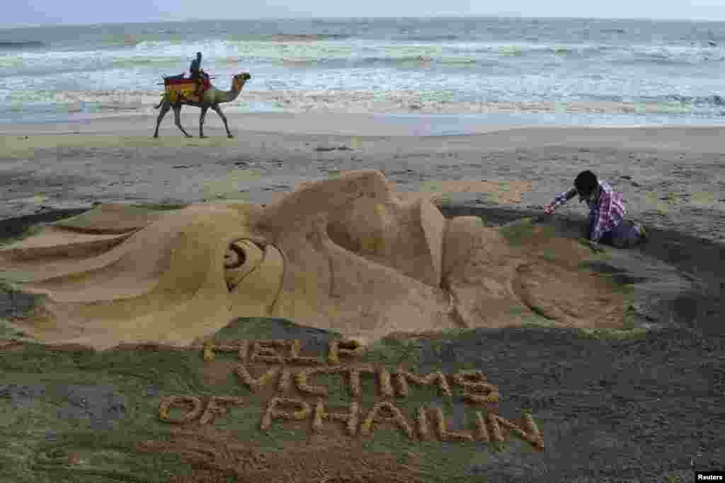 Sand artist Sudarshan Pattnaik works on a sculpture about Cyclone Phailin that hit Puri in the eastern Indian state of Odisha.