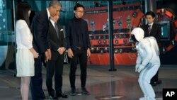 24일 일본을 방문 중인 바락 오바마 미국 대통령(왼쪽 두번째)이 도쿄 에너지과학박물관에서 로봇과 서로 인사하고 있다.