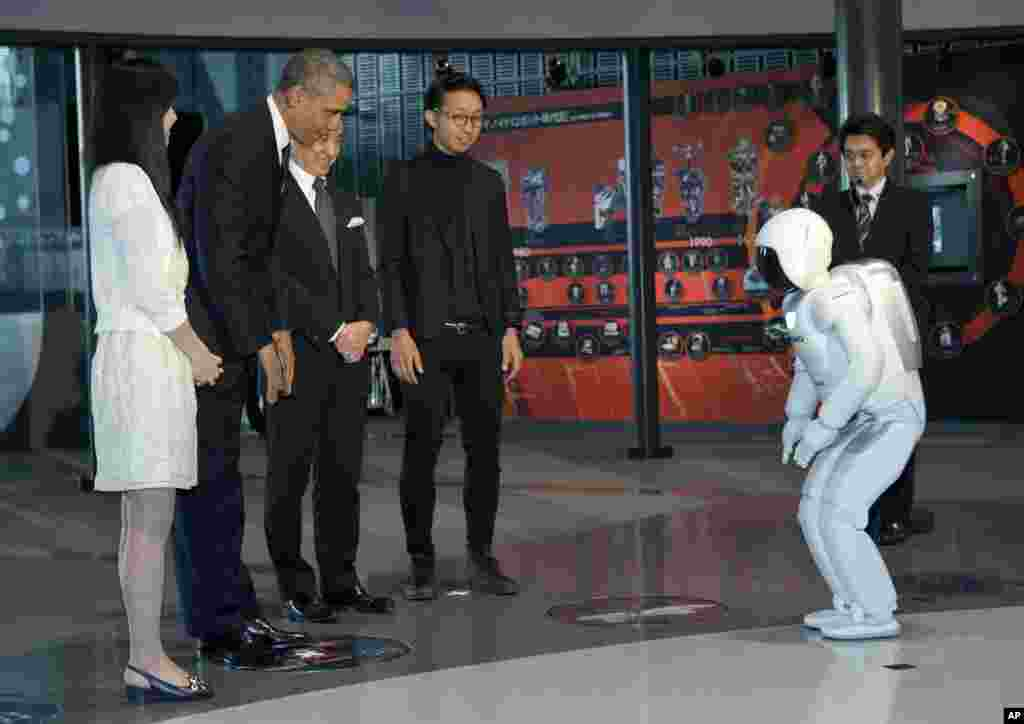 President Barack Obama and ASIMO, an acronym for Advanced Step in Innovative MObility, bow to each other during a youth science event at the National Museum of Emerging Science and Innovation in Tokyo, April 24, 2014.