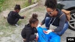 یک خانواده داوطلب در حال جمع کردن زبالههای ساحل رودخانه پوتومک در شهر الکسندریا، ویرجینیا