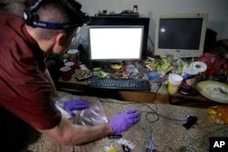 2017年4月20日,在菲律宾马巴拉卡特,在对来自伊利诺伊州皮奥里亚的蒂莫西·迪肯的一次突袭行动中,联邦调查局的电脑分析师在这位涉嫌从事儿童网络色情的运营商的电脑进行检查