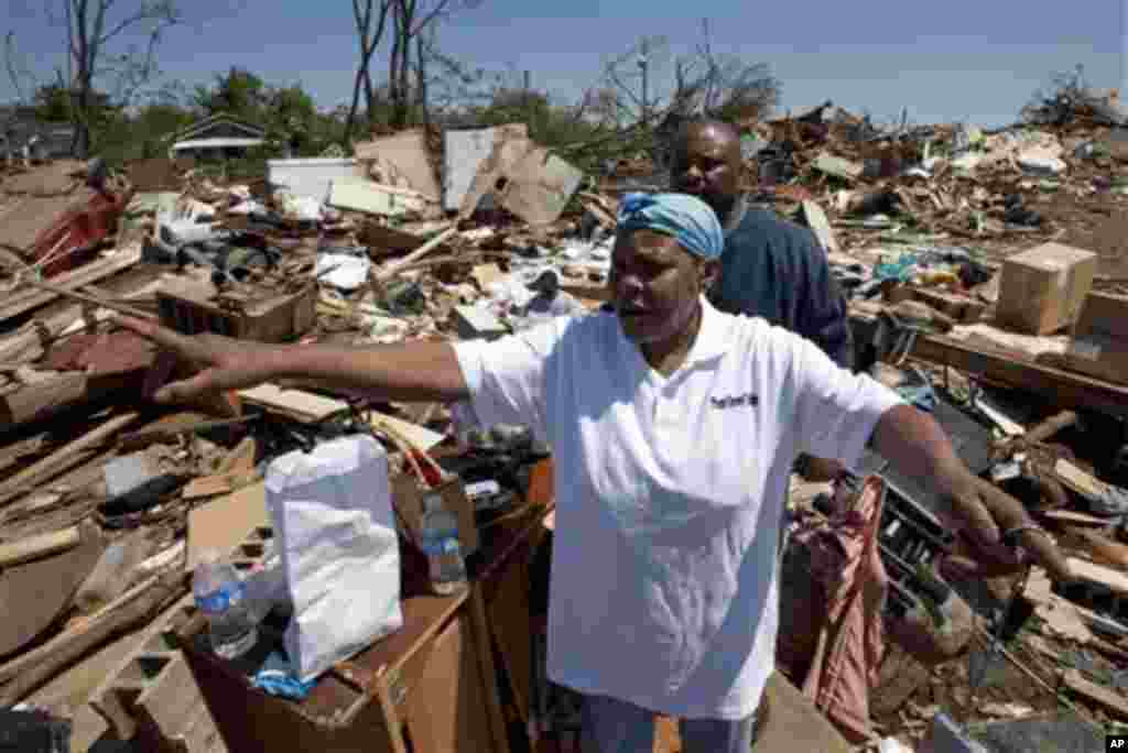 Elizabeth Williams points out where the tornado came from as she stands among the debris of her home in Tuscaloosa, Ala., Friday, April 29, 2011. Williams, two sons and a daughter survived the storm by hiding together in a closet. They watched the tornad