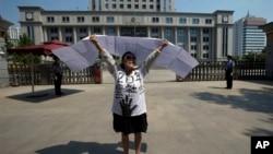 2013年8月21日,一名女子在濟南中級人民法院前抗議。對薄熙來的審判引來一些抗議和上訪者,有人挺薄,也有人借機訴說自己的冤情