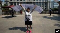 2013年8月21日,一名女子在济南中级人民法院前抗议。对薄熙来的审判引来一些抗议和上访者,有人挺薄,也有人借机诉说自己的冤情。