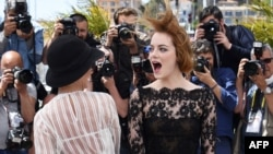 "US actresses Parker Posey (L) and Emma Stone pose during a photocall for the film ""Irrational Man"" at the 68th Cannes Film Festival in Cannes, southeastern France, on May 15, 2015."