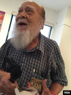 96岁的何天开老人展示文革劳改犯标识(美国之音方冰拍摄)