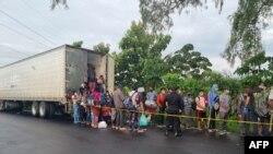 Migrantes que viajan en un camión de carga en un intento de llegar a la frontera con los Estados Unidos se bajan luego de que el camión fuera detenido por la Policía Nacional Civil de Guatemala (PNC), en Mazatenango, Guatemala.
