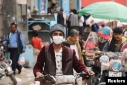 A man wears a protective face mask as he rides a motorcycle amid fears of the spread of the coronavirus disease (COVID-19) in Sana'a, March 16, 2020.