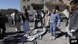 Warga Yaman berkumpul di dekat seorang korban tewas akibat serangan udara Saudi di ibu kota Sanaa, Rabu (13/12).