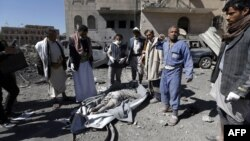 Yemeni Huthis gather around the body of a man killed by airstrikes at a detention center in the capital Sanaa, Dec. 13, 2017.