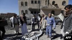 13일 예멘 수도 사나에서 사우디 주도 연합군의 공습이 있은 후 후티 반군이 사망자 시신을 수습하고 있다.