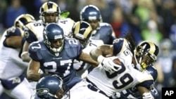 St. Louis Rams' Steven Jackson runs the ball as Seattle Seahawks' Jordan Babineaux (27) and Kentwan Balmer (95) attempt the tackle in the first half of an NFL football game, 2 Jan. 2011, in Seattle.